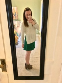 green high-waisted skirt with ivory sweater with high slit